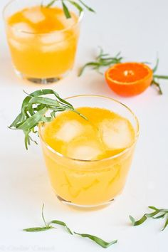 Clementine & Lemon Gin Cocktail Recipe -- clementine, lemon and lim juice combine with sparkling lemon flower soda and gin to make this refreshing winter citrus cocktail, garnished with a sprig of fresh taragon for an aromatic herbal scent. Love how refreshing and low-calorie this drink is! Perfect for meeting those healthy New Year's Resolutions!