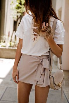 Cute white laced front top with blush wrapped skirt and chic blush handbag.