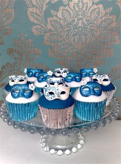 Hand-painted blue and white Venetian mask cupcakes for a masquerade wedding.