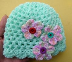"Cute little beanie with scalloped trim and three little multicolored flowers with button centers. Approx. 12"". Best if you make your own measurements of your little ones head to ensure correct sizing. Item #8266"