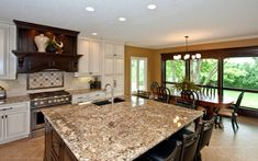 An elegant kitchen with an adjacent dining room. The busy brown and cream granite countertops are contrasted by the light, subtle backsplash. Brown Granite Countertops, Best Kitchen Countertops, Kitchen Colors, Kitchen Backsplash, Backsplash Ideas, Kitchen Cabinets, Kitchen Cupboard, Island Kitchen, Kitchen Layout
