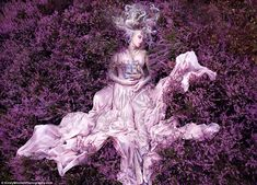 Gammelyn's Daughter. the model clutches a ship to her chest amidst a heathery cushion  Part of a set of gorgeous photos by Kirsty Mitchell.