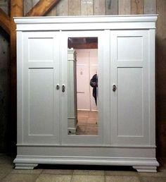Witte oude kledingkast met spiegel middenin. Wit is niet de meest geschikte kleur voor zo'n kast