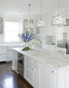 White kitchen with marble benchtops, dark floors and white and chrome pendant lights