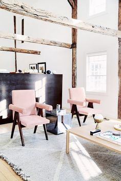 Living space with exposed wooden ceiling beams, a smoked mirrored cube, and pink armchairs
