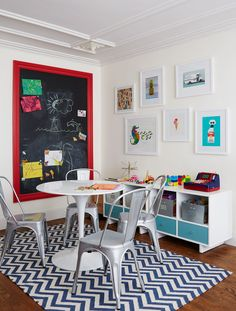 A colorful arts-and-crafts area in the playroom is delineated by a zigzag-pattern dhurrie from Pottery Barn and a custom-made chalkboard framed in Benjamin Moore Poppy paint. | Lonny.com