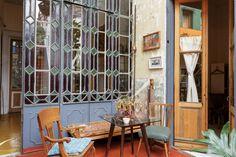 Antigua casona rústica reciclada como residencia de artistas. Gran ventanal de vidrio repartido con dibujos y puertas de madera en el patio.