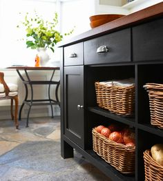 """Create Island Organization while adding beauty and smart function to a small kitchen. """"Island storage doesn't need to be enclosed. Removing a few cabinet doors from this island provides easy access to items while adding an open feel to the small kitchen work space. Wicker baskets corral the contents of each shelf to ensure everything stays neat and tidy."""""""