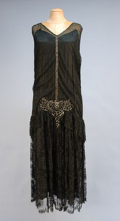 1920's.BEADED BLACK LACE DANCE DRESS, Sleeveless with V-neck mesh over satin bodice, dropped waist, full lace skirt having hip flounce, satin and chiffon underskirts, scalloped hem, the neckline and waist decorated with rhinestones, pearls and crystal beads.