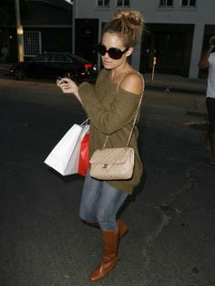again with the off the shoulder look: jeans, boots, long sleeve off the shoulder shirt/sweater, long purse, bun