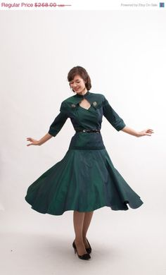 Vintage 1950s Sharkskin Green Taffeta Dress 1/2 Length Sleeves Lightly Padded Shoulders Bands of Tight Pleating at the Neckline, Below the Shoulders and Above the Hips Natural Fitted Waist and a Drop Waist with a Full Skirt Side Metal Zipper Neckline Closes with a Diamond Shape Cutout - Two Large Rhinestone Brooches (sewn on) at Both Sides of the Upper Bust String Belt Loops (belt shown is not included)