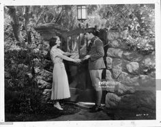 Fredric March holding Norma Shearer's hand in a scene from the film 'Smilin' Through', 1932.