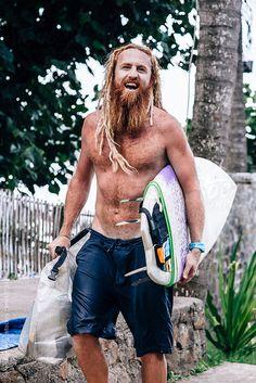 Portrait of red bearded surfer carrying his surfboard by Soren Egeberg #stocksy #realstock