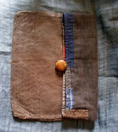 hand sewn pouch in antique Japanese cottons in beautiful rustic, earthy tones : striped cottons, antique sake bag with a great patina (sakabukuro, dyed with persimmon, used in the sake making process : anti bacterial properties), applique in indigo cotton and hemp and brown linen the inside lining is in Indian blockprint cotton, naturally dyed it closes with a loop in linen twine and a vintage button dimensions closed : width 25,7 cm x height 20,5cm approx open : width 25,7 cm x height 29...