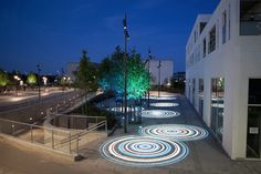 "The lighting design for Ishoj Station in Copenhagen combines functionality with creating a water theme for the courtyard. Trees are lit in blue and green lights, while eight water ""ripples"" are created by shining blue and white lights on the ground. - photo from illumni;  lighting designer was F Hansen & Henneberg"