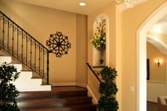 Sophisticated stairway design with dark wood floors and wrought iron railings. From 1 of 30 projects by Gelotte Hommas.