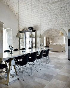 dining space under a white painted brick barrel vault, paved floor, Eames DSR side chairs with Eiffel base and table with trestle legs