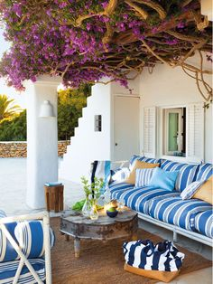Fresh striped outdoor seating, shaded by bougainvillea.