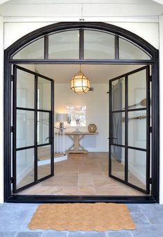 A woven mat on a slate floor leads to steel and glass double doors opening to a chic foyer filled with a light wood console table illuminated by a Suzanne Kasler Morris Lantern.