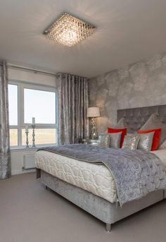 Luxurious master bedroom in grey accents with velvet curtains, bed and throw and beautiful wallpaper! Bright and airy with full wall windows. Glamorous chandelier and silver and orange cushions to complete this singular room in Scotland!