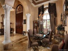 Dramatic formal dining room - crystal chandelier - grand marble columns.  Grey Oaks in Naples, Fl