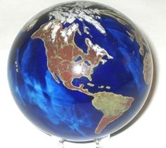 """Lundberg Studios World Weight Extra with oceans in cobalt blue. Clear views of the continents Hawaiian Islands, clouds and northern polar snow caps. Flat bottom allows for display without use of pedestal. Artist signed dated and numbered. Approximately 4.25"""" diameter."""