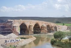 """Cobandede Arc Bridge, Turkey (1295-1304), was in the process of being restored but the Government managed to collapse one of the 700-year old arches instead! Part of the ancient silk route, Cobandede Bridge is on the Aras River that makes a """"T"""" around Ani where it meets another river to form boundaries between Armenia and Turkey."""