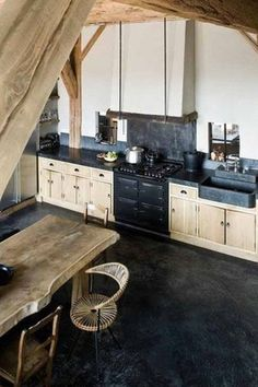 Rustic Kitchen with Soapstone counters, Standard height, partial backsplash, gas range, Built In Refrigerator, Exposed beam