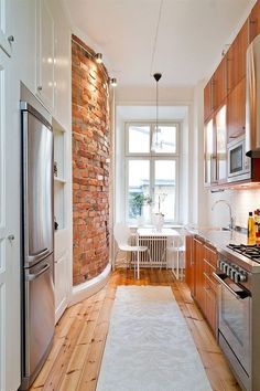 Narrow Kitchen With Exposed Brick, Wood Floor, Timber Cupboards And Window  Seating