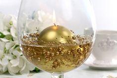 Improvisa bonitos, diferentes y elegantes centros de mesa!  Te voy a hacer una sugerencia. Llena de agua hasta la mitad aproximadamente un copón, una pecera o cualquier centro de mesa de cristal transparente, situa en el fondo la Guirnalda Perlas Oro y mete Velas Flotantes.