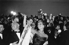 Les photographes de Paris Match à l'honneur.  Rendez-vous le 3 mai pour un événement exceptionnel avec la prestigieuse Maison de ventes Cornette de Saint Cyr. Découvrez en avant-première les plus belles photos de notre vente.  LOT 71 Michou Simon (1931-2002) et Claude Azoulay (1934). Lors du 11e Festival de Cannes, l'arrivée de Sophia Loren, Carlo Ponti et Robert Favre Le Bret, délégué général du Festival. 3 avril 1958. 52 x 78 cm. Tirage postérieur sur papier baryté. Encadrement bois noir…