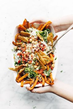 {Sweet potato fries topped with fresh romaine, tzatziki, marinated tomatoes and chickpeas and feta cheese.}