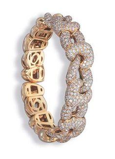 A DIAMOND BANGLE, BY BOUCHERON  The pavé-set diamond intertwined heart-shaped links to the polished 18k gold sides, 5.3 cm. diameter Signed Boucheron, no. P6047
