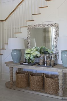 Chic cottage foyer features wainscoted staircase wall framing an oval console table filled with three round woven baskets and topped with watery blue table lamps flanking trays filled with vases filled with peonies and a martini set under a large rectangular seashell encrusted mirror.