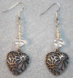 Handcrafted by Teal Palmetto, LLC. Silver filigree hearts are the focals in this romantic pair of earrings. Each one is topped with a sparkling clear glass crystal bead. Silver fish hook ear wires complete the look. Price: $13.