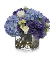 This largely blue with a bit of white and green wedding centrepiece is really lovely -from flower-arrangement-advisor.com