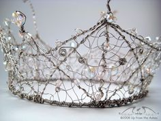 """This crown is a full circle of silver artistic wire, meticulously hand-crafted with three different gages, encrusted with swarovski and fire-polished crystals, all hand-woven together to resemble swirling metallic lace. Many many labor intensive hours we carefully worked into this piece, giving you a sturdy crown of heirloom quality.  Measures 16.5"""" (41.9cm)in circumference, this little beauty is worn perched atop your head-rakish angle optional. Stands 6"""" (15.2cm) tall with a diameter of…"""