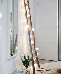 a ladder made using cut branches becomes a decorative feature - inexpensive and dramatic - with string fairy lights and ping pong balls