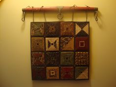 "Sue's original folded log cabin  16 squares with tons of earth-tone fabrics  Beads added at intersections  Hung with red/iron singletree  Now hanging at Eagle Creek Quilt Shop--soon to be ""home"""