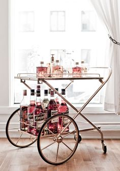 The swedish fashion designer of the year, Carin Rodebjer, opens up her office to Elle..shades of pink and red does the pretty bar cart make!