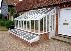 Lean to greenhouses and solariums are a wonderful architectural feature that you can grow food in. See some lean to greenhouse plans, inspiration for solariums, lean to greenhouses with water collection and cold frames and building and design tips. Lean To Greenhouse Kits, Greenhouse Plans, Greenhouse Gardening, Greenhouse Wedding, Greenhouse Attached To House, Small Greenhouse, Greenhouse Kitchen, Greenhouse Frame, Winter Greenhouse