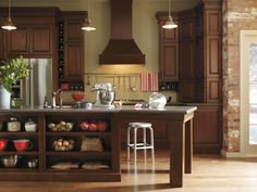 We're thankful for extra countertop space, especially when it's our turn to host Thanksgiving! The extended kitchen island with storage cubbies is a unique way to maximize space for cooking, and is also ideal for gathering loved ones on special days. #SchrockKitchens   Featured: Schrock's Carmin cabinets in a Black Forest finish.