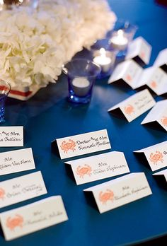 Nautical Red Crab Stamped Escort Cards. The escort-card table incorporated the couple's colors via blue votives, white hydrangeas, and red ink-stamped cards.
