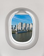 Looking out the window of a plane to the skyscrapers
