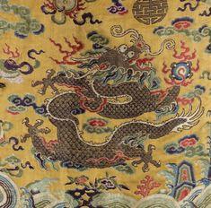 """ROBE """"mang pao"""" (robe pour les membres de la famille impériale) en soie jaune finement brodée aux fils dorés et polychromes de huit dragons à quatre griffes, figurés de face ou de profil, parmi des nuages stylisés et des symboles auspicieux. La partie inférieure de la robe est décorée d'une large bande de """"lishui"""" surmontée de vagues tourbillonnantes et des pics sacrés. La bordure des manches et du col est ornée de dragons marchant alternant avec des dragons de face sur fond brun. Chine…"""