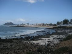 Northwestern rockier beaches of Corralejo, Spain with the Isla de los Lobos in the background