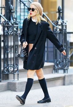 Chloe Sevigny wears a sweater, collared shirt, skirt, black coat, Louis Vuitton bag, knee-high socks, loafers, and a fuzzy beret with black sunglasses