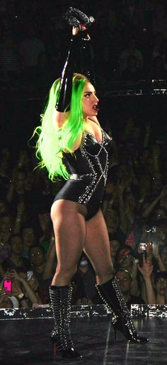 Lady Gaga with green hair strikes a pose.  A performer doing life, and music on her terms.  Check out one of her shows today!