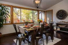 As seen on Vacation House For Free, the wood trim around the windows in the dining room echoes the wood accents placed throughout the house. The gray door leads to a second bathroom.