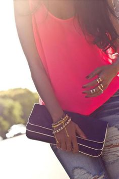 Neon pink tank, blue jeans, gold accessories, black clutch all scream spring